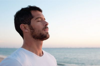Mind Your Body Co - Man deep breathing in front of ocean